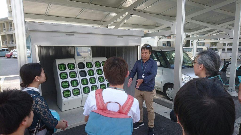 産能大学の生徒に電動バイク充電ステーションで説明